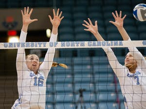Grad Student Right Side Emily Zinger (16) and Senior Middle Hitter Amanda Phegly (7) jump to block the ball in the UNC win against Elon University on September 14, 2021.