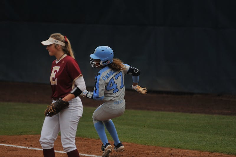 (From left) Elon first baseman Megan White (12) and UNC Destiny Middleton (47) watch as Middleton's hit is in the field during a game against Elon on Wednesday, Feb. 26, 2020 in G. Anderson Softball Stadium. UNC lost to Elon 2-1.