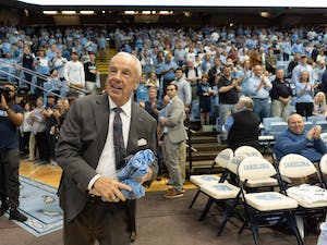 Roy Williams tosses T-shirts before the game against Yale on Monday, Dec. 30, 2019 in the Smith Center. UNC defeated Yale 70-67, marking Williams' career high of 879 wins, a tie with former head coach Dean Smith.