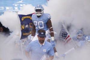 Head coach Larry Fedora and his players take the field for a game against California on Saturday. Nort Carolina lost, 35-30.