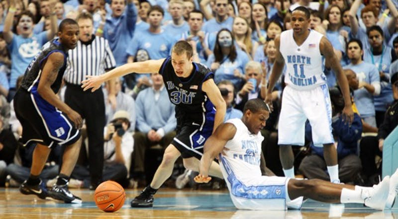 Duke guard Jon Scheyer slides past UNC senior forward Deon Thompson for a loose ball in Duke's 64-54 victory. DTH/Phong Dinh