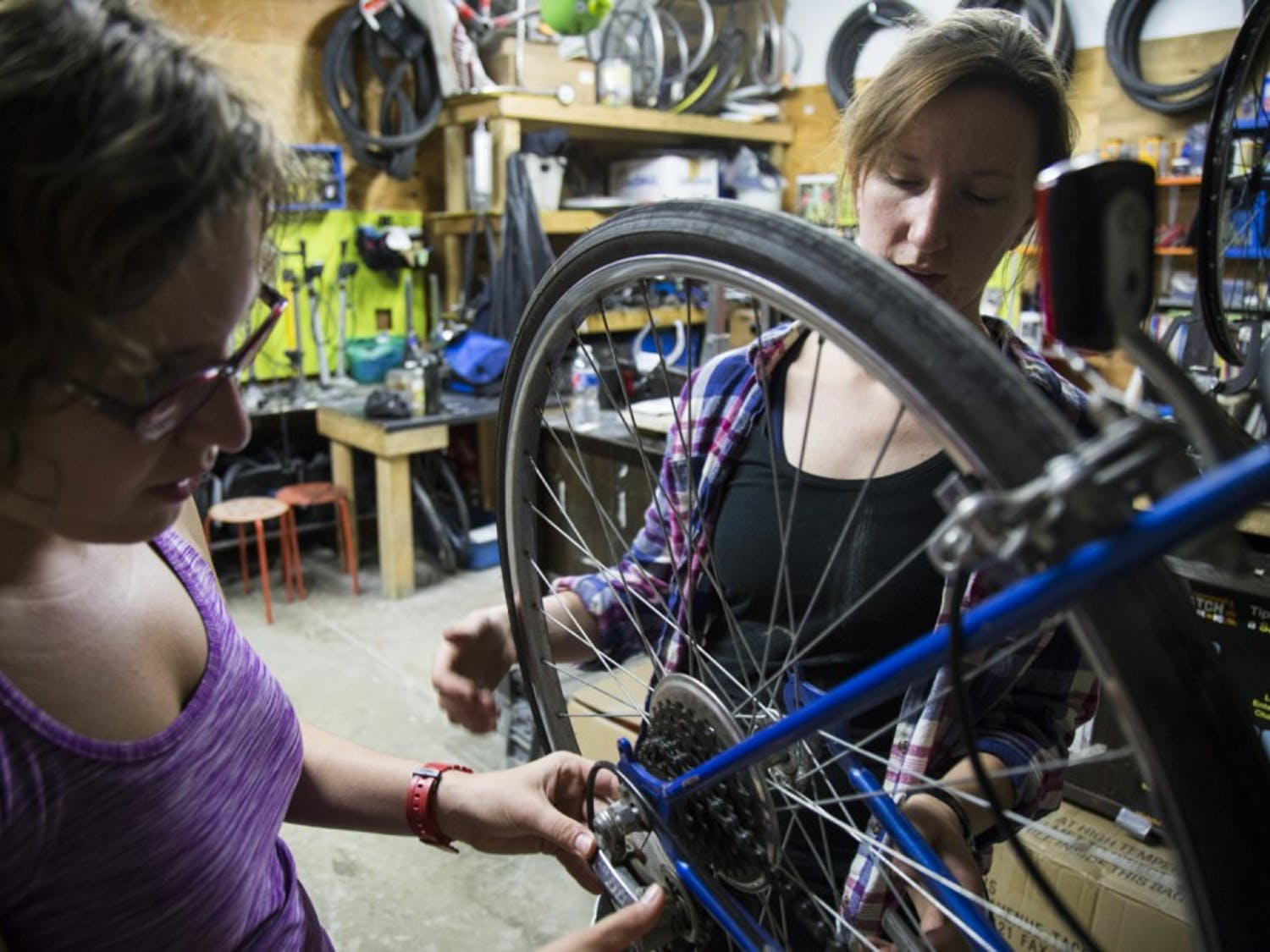 Victoria Petermann (right) helps Maia Call make adjustments on her bike, which she bought six years ago on Craiglist.