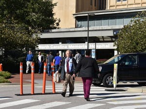 Groups of people enter and exit the N.C. Memorial Hospital, one of several UNC Hospitals.