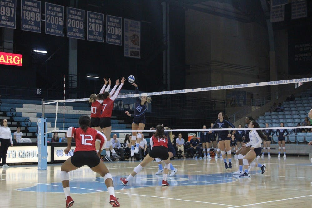 <p>Outside Hitter Ava Bell (20) spikes the ball against Louisville players Melanie McHenry (10) and Emily Scott (7) on Sunday, Sept. 23, 2018 in Carmichael Arena.&nbsp;</p>