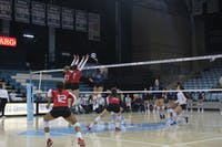 Outside Hitter Ava Bell (20) spikes the ball against Louisville players Melanie McHenry (10) and Emily Scott (7) on Sunday, Sept. 23 in Carmichael Arena.