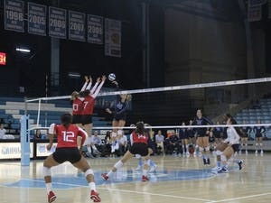 Outside Hitter Ava Bell (20) spikes the ball against Louisville players Melanie McHenry (10) and Emily Scott (7) on Sunday, Sept. 23, 2018 in Carmichael Arena.