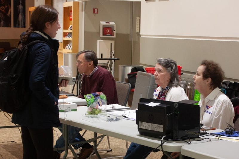 Country Club precinct's Chief Judge Carol Hazard, Democratic representative Barbara Wendell and Republican representative Robert David work the check-in table at the Paul Green Theatre on Tuesday, Nov. 5, 2019.