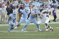 UNC junior tight end Jake Bargas (80) defends against WCU redshirt first-year linebacker Bruce Squires (34) as first-year safety Drew Homschek (19) goes in for a recovery on Saturday, Nov 17., 2018, in Kenan Memorial Stadium. The Tar Heels won 49-26 against Western Carolina.