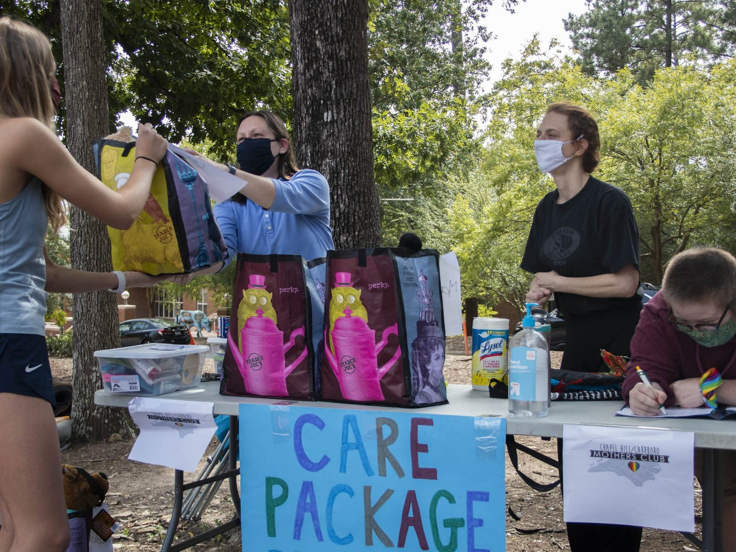 "(From left) Lynne Privette, Jamie Sohn and Tiz Giordano hand out care packages to a first-year outside of the George Watts Hill Alumni Center on Wednesday, Sep. 16, 2020 through Chapel Hill/Carrboro Mothers Club. Over 35 students received personalized packages and community members made 75 homemade masks in support of the initiative. ""The average care package weighed about seven pounds,"" Sohn said."