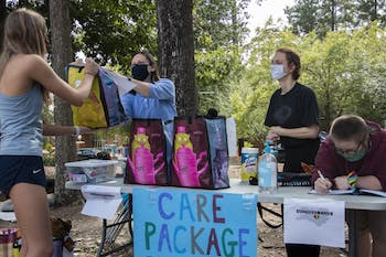 """(From left) Lynne Privette, Jamie Sohn and Tiz Giordano hand out care packages to a first-year outside of the George Watts Hill Alumni Center on Wednesday, Sep. 16, 2020 through Chapel Hill/Carrboro Mothers Club. Over 35 students received personalized packages and community members made 75 homemade masks in support of the initiative. """"The average care package weighed about seven pounds,"""" Sohn said."""