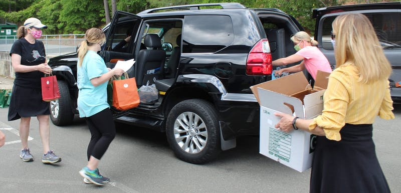 Volunteers for Book Harvest load food and books into cars to be delivered to families across Durham in a collaborative effort with the Durham Public Schools Foundation and Durham FEAST.