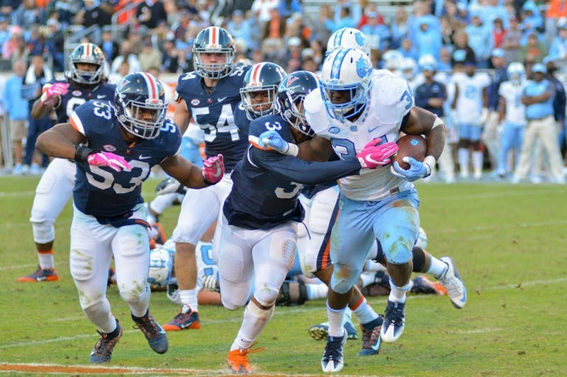 Elijah Hood (34) fends off a Virginia defender. UNC defeated UVA 35-14 on Saturday, October 23.