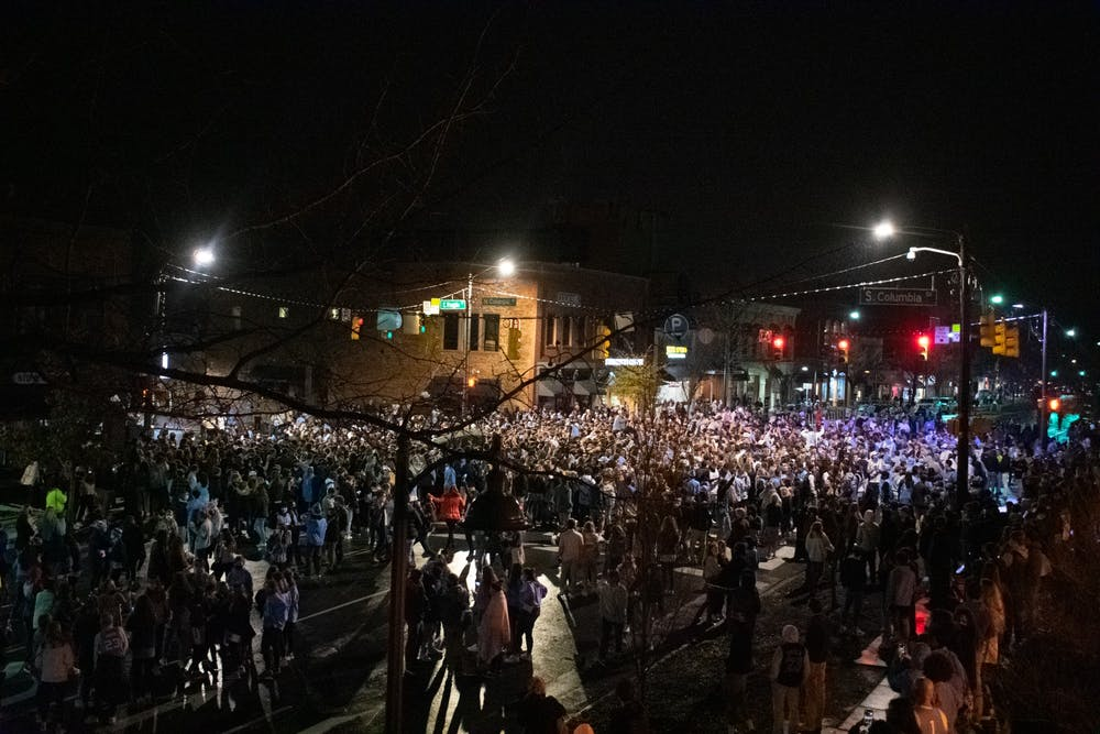 <p>Students rush Franklin Street following UNC's 91-87 mens basketball victory over Duke. Hundreds of students gathered at the intersection of Franklin and Columbia despite COVID-19 restrictions.</p>