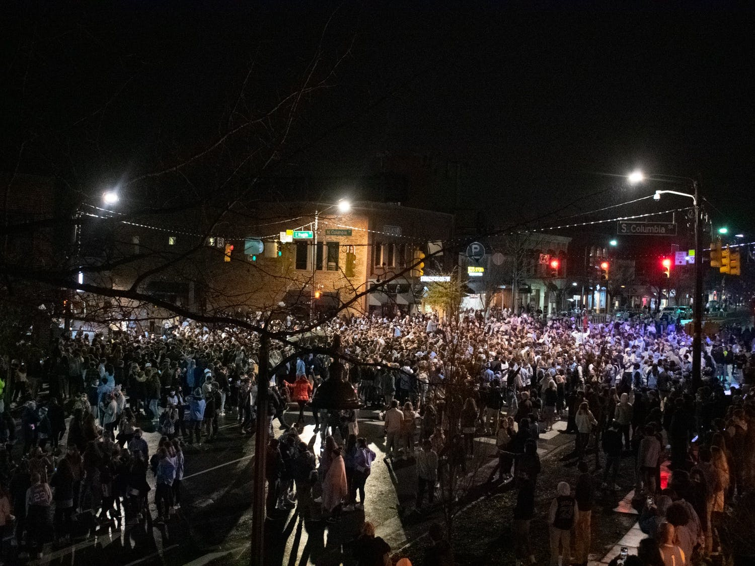 Students rush Franklin Street following UNC's 91-87 mens basketball victory over Duke. Hundreds of students gathered at the intersection of Franklin and Columbia despite COVID-19 restrictions.