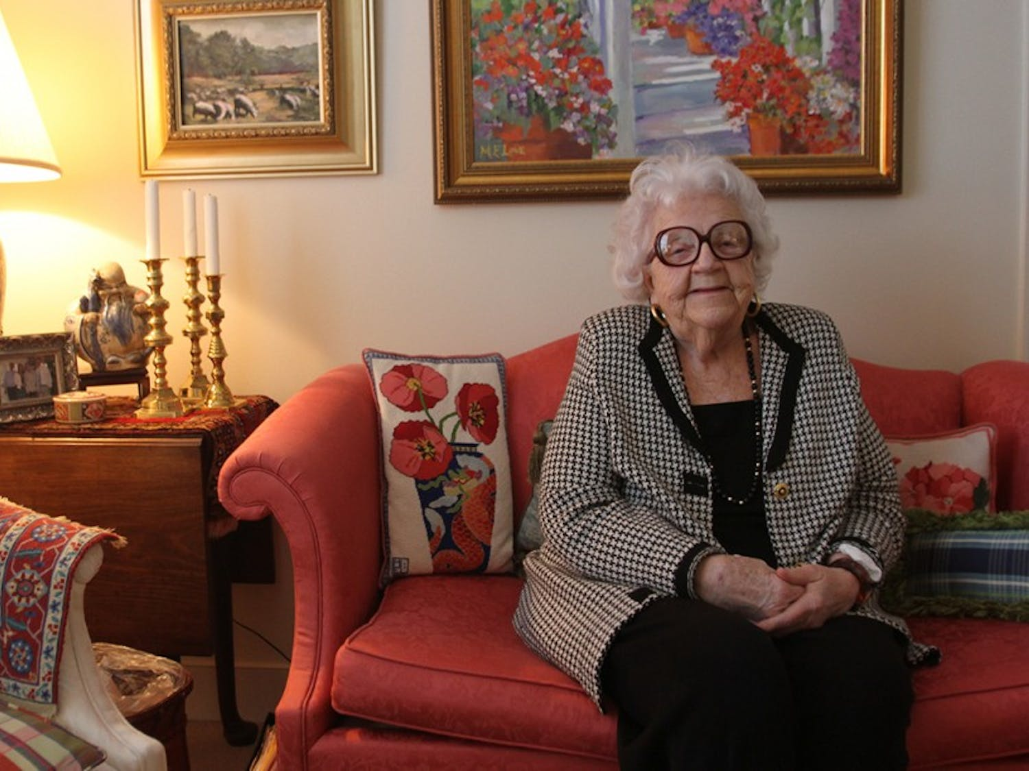 """Maggie Love, 88, paints """"happy paintings"""" that are now on display at University Mall. She has macular degeneration and is starting to lose her eyesight, which makes painting more difficult. She continues to paint and now does more abstract work. Love poses with her artwork in her home at Galloway Ridge retirement community at Fearrington."""