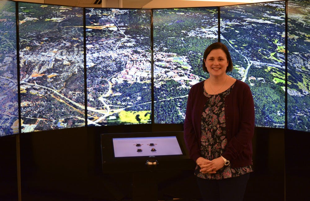 <p>Amanda Henley stands in front of Davis Library's Liquid Galaxy, with the city of Chapel Hill pictured.</p>