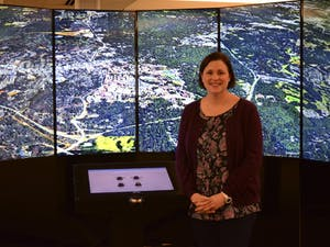 Amanda Henley stands in front of Davis Library's Liquid Galaxy, with the city of Chapel Hill pictured.
