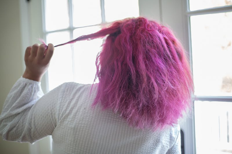 DTH Photo Illustration - A young woman shows off her pink dyed hair.