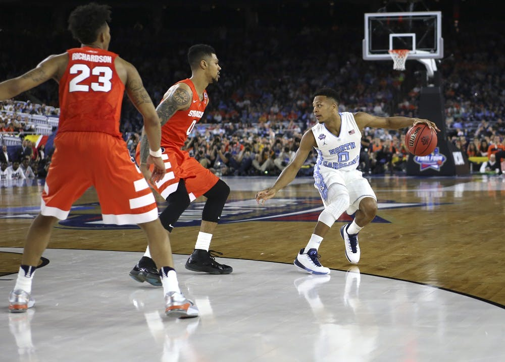 <p>UNC guard Nate Britt (0) takes on two Syracuse players during the semi-final NCAA Tournament game.&nbsp;</p>