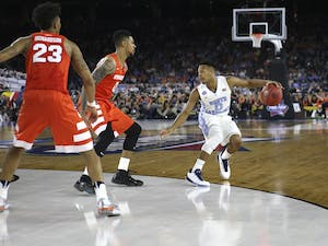 UNC guard Nate Britt (0) takes on two Syracuse players during the semi-final NCAA Tournament game.