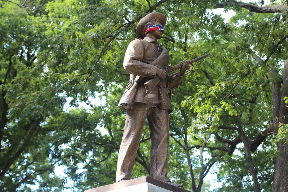 <p>Silent Sam blindfolded by a Confederate flag in 2015. The statue was recently given to Sons of Confederate Veterans.</p>