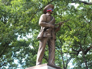 Silent Sam blindfolded by a Confederate flag in 2015. The statue was recently given to Sons of Confederate Veterans.