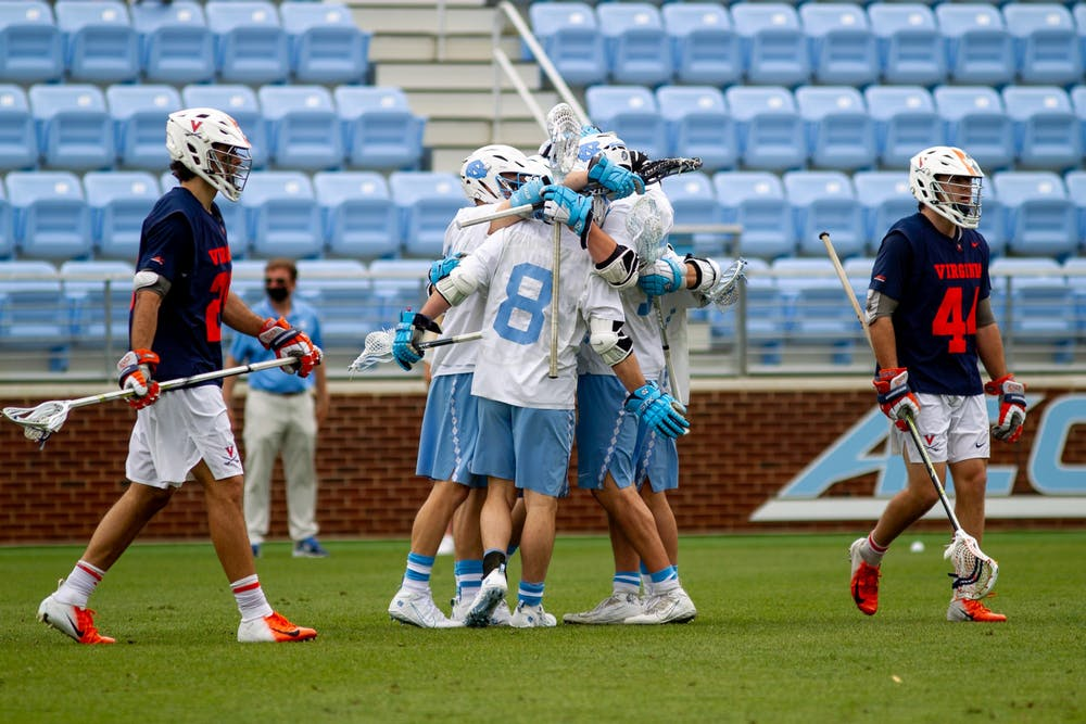 Members of the UNC men's lacrosse celebrate a goal during an 18-16 loss to UVA at Dorrance Field on April 10, 2021.