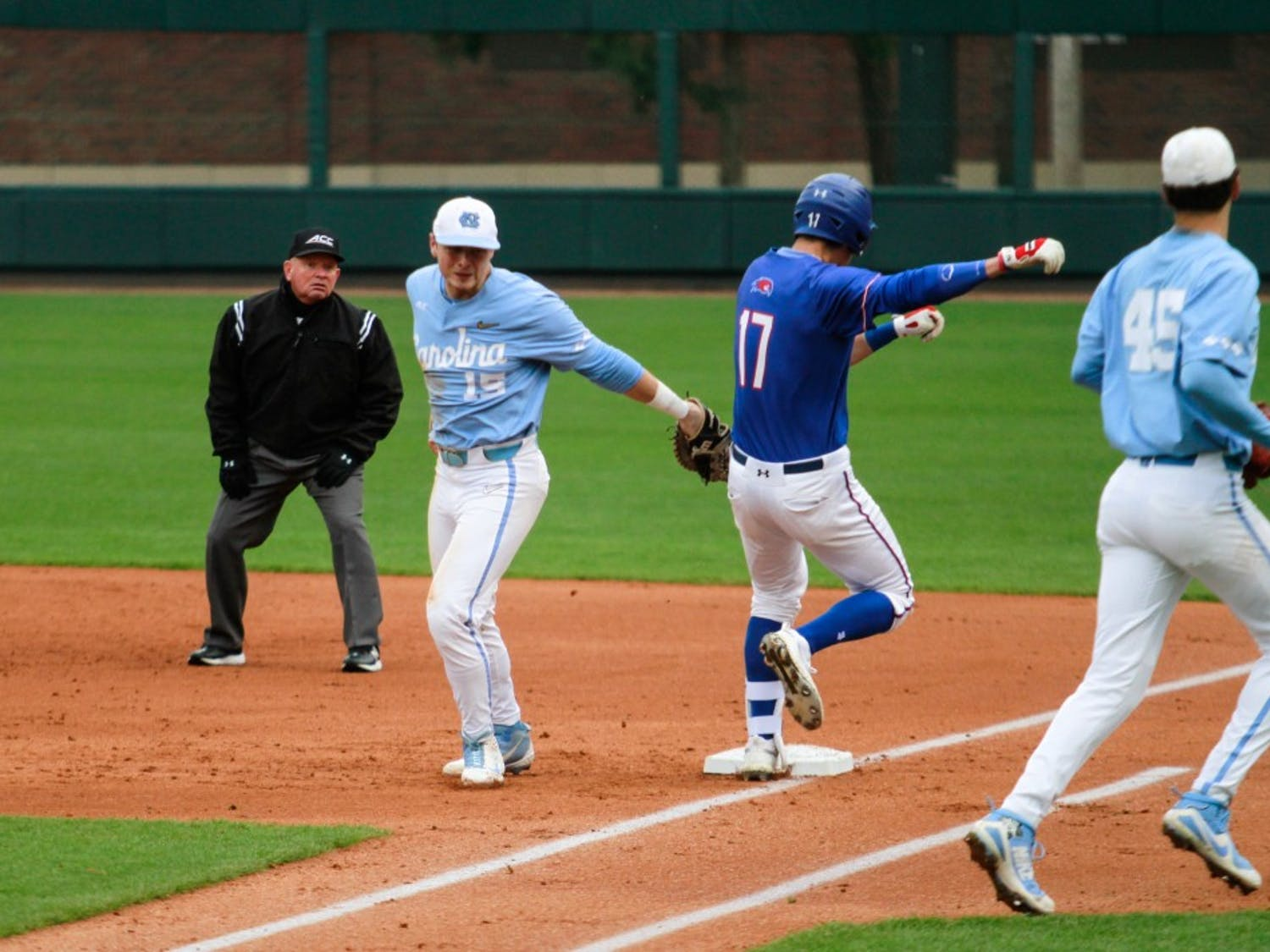 UNC first baseman junior Michael Busch (15) attempts to tag an opponent out leading to a disputed call gainst UMass Lowell on Sunday, March 3, 2019 at Boshamer Stadium.