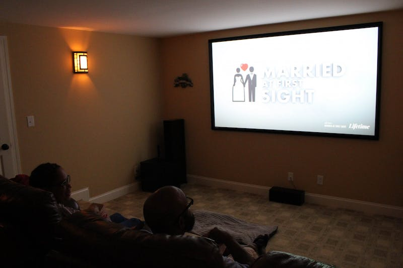 """DTH Photo Illustration. People watch """"Married at First Sight"""", a reality TV show on Lifetime TV. Over quarantine, many people have turned to various dating shows to stay entertained."""