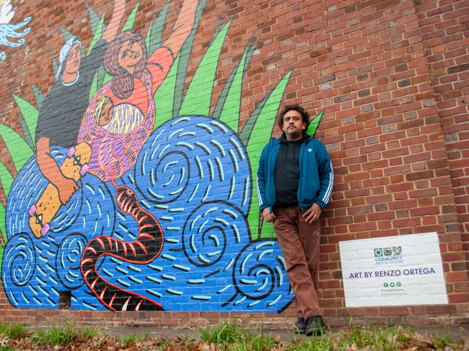 """Renzo Ortega poses for a portrait with his work """"Successions"""". The new mural at TOPO Distillery pays tribute to family bond dynamics, especially those of family members that have left and have yet to return."""