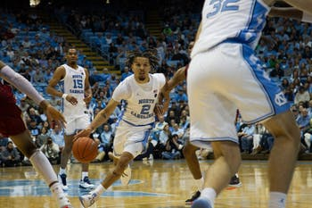 First-year guard Cole Anthony (2) dribbles past opposing players in basketball game against Elon University on Thursday, Nov. 20, 2019. UNC won 75-61.