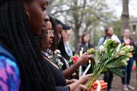 (From left to right) Kira Griffith, sophomore neuroscience major, Gabrella Behailu, sophomore media and journalism and communication studies major and Tsion Coulter, computer science major, hold candles at the Unsung Founders Memorial vigil, Thursday April 4, 2019 at McCorkle Place. The vigil was in response to the defacement of the memorial Sunday, March 31, 2019.