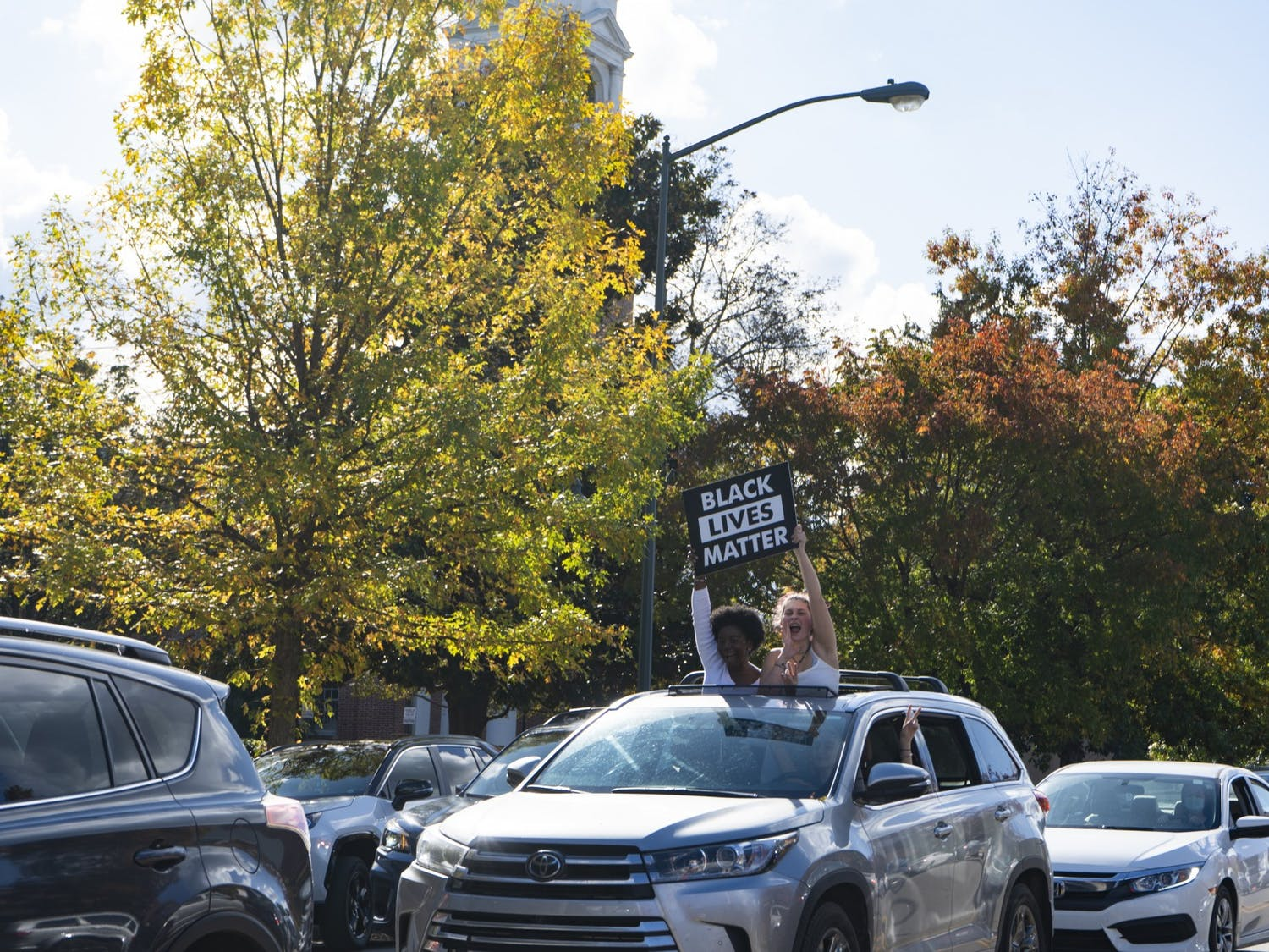 Amidst honking cars, music and shouting, students hold a Black Lives Matter sign as they drive east on Franklin Street the afternoon of the announcement that Former Vice President Joe Biden has won the presidential race on Saturday, Nov. 7, 2020.