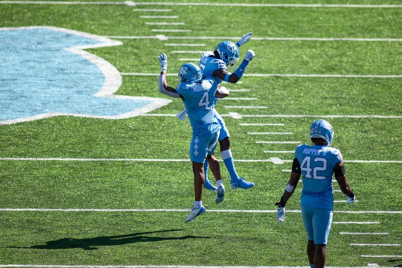 UNC junior defensive back Trey Morrison (4) and sophomore defensive back Ladaeson DeAndre Hollins (15) celebrate after a tackle in Kenan Stadium Oct. 24, 2020. The Tar Heels beat the Wolfpack 48-21.