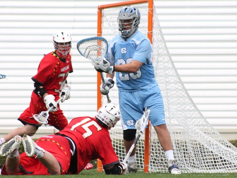 UNC goalkeeper Kieran Burke (26) defends a goal from a Maryland player. UNC won 11-8.