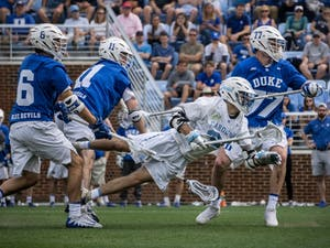 UNC junior midfielder William Perry (3) falls down after making a pass upfield Saturday, March 30, 2019 in their game against Duke.  The Tar Heels won 10-8 at the UNC Lacrosse Stadium.
