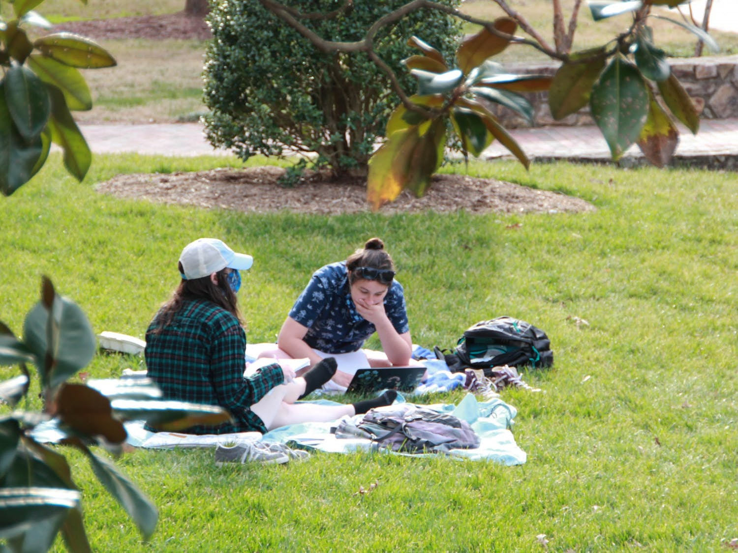 Two students study on the quad on March 9, 2021.