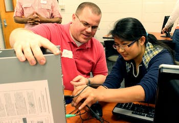 Hla Win Tway, a 8th Grader/15 years old girl studying at Smith Middle School, is connecting the monitor to the main body under the instruction of the volunteer, Mr. Alan Brown, who is a technical specialist for Northside Elementary School. He lives in Morrisville.
