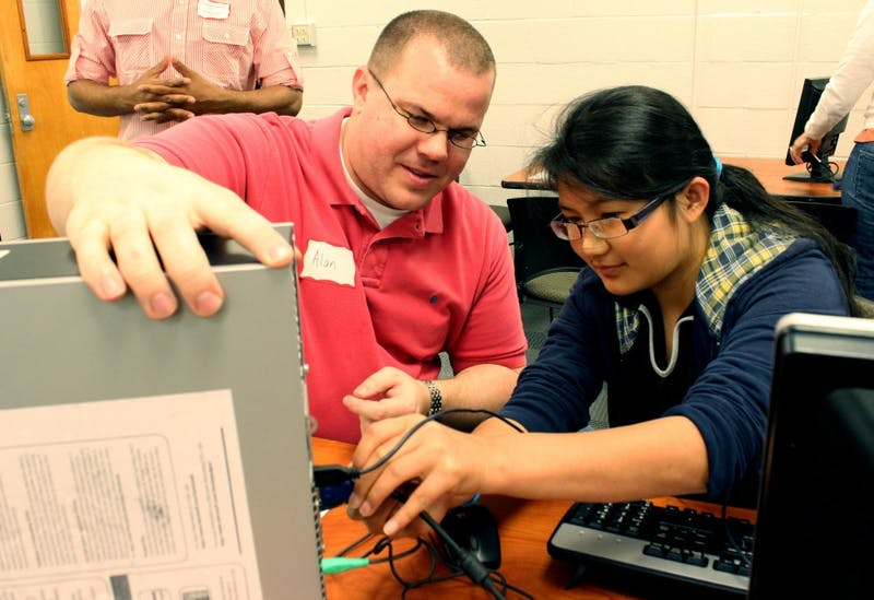 Alan Brown, a technical specialist for Northside Elementary School, volunteers at Saturday's computer distribution while 15-year-old Hla Win Tway, an eighth grader at Smith Middle School, learns to connect the monitor of the computer to the main body.