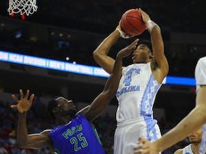 Isaiah Hicks shoots the ball over Marc0Eddy Norelia.