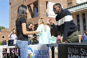 Roderick Gladney (right), founder and chairman of Carolina Cupboard, an organization that provides free food to the UNC campus community, helps recruit new members in the Pit in October.