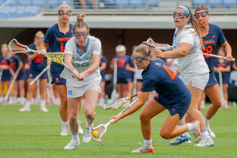 UNC first year midfielder Shannon Smith attempts to get the ball from a Virginia player at the game against Virginia on Sunday Apr. 18, 2021 at the Dorrance Field. UNC won 15-4.