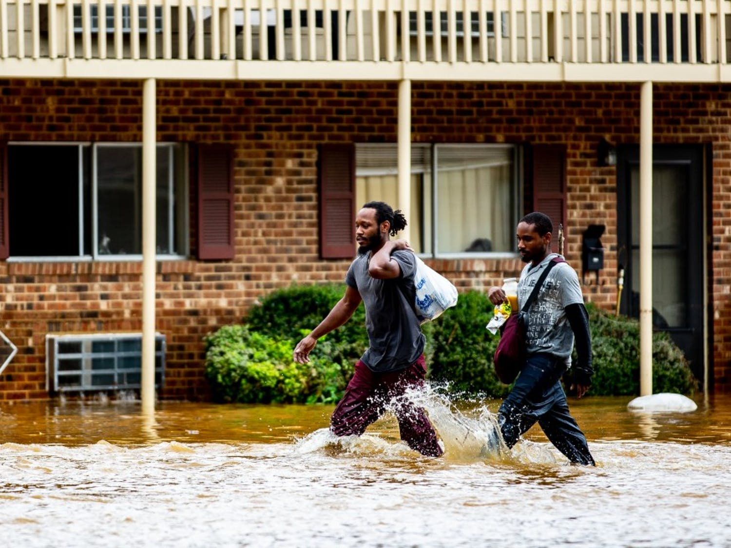 """Kyrie and Michael Benton carry food and some of their waterlogged belongings through the grounds of Camelot Village apartments in Chapel Hill the morning of September 17, 2018. Chapel Hill had been seemingly spared the worst of Hurricane Florence but Sunday night into Monday morning saw a downpour of heavy rain that caused flash flooding around the Triangle. Camelot Village has seen flooding in the past but never to this degree, according to Kyrie and other residents of many years. """"I lost everything in this flood,"""" Kyrie said. Just as quickly as it flooded, the water began to recede late the same morning and early in the afternoon."""