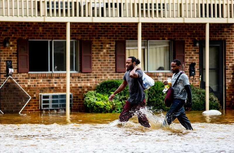 "Kyrie and Michael Benton carry food and some of their waterlogged belongings through the grounds of Camelot Village apartments in Chapel Hill the morning of September 17, 2018. Chapel Hill had been seemingly spared the worst of Hurricane Florence but Sunday night into Monday morning saw a downpour of heavy rain that caused flash flooding around the Triangle. Camelot Village has seen flooding in the past but never to this degree, according to Kyrie and other residents of many years. ""I lost everything in this flood,"" Kyrie said. Just as quickly as it flooded, the water began to recede late the same morning and early in the afternoon."