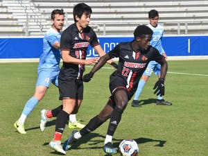 Louisville junior Kino Ryosuke (9) helps his teammate Cherif Dieye (12) escape from UNC defense in the ACC championship game on Sunday, Nov. 11, 2018. UNC lost to Louisville 0-1.
