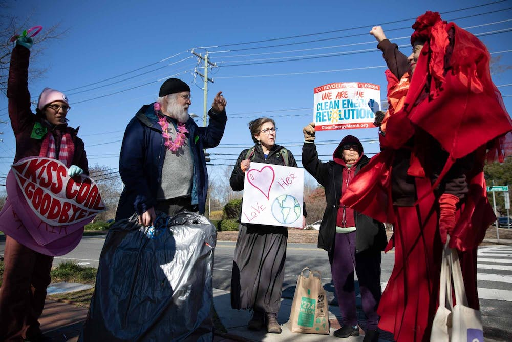 <p>Members of the community protest in front of the coal power plant on Cameron Avenue on Friday, Feb. 14, 2020. The protestors have gathered here every Friday morning since May 2019 to protest the coal plant operation.&nbsp;</p>