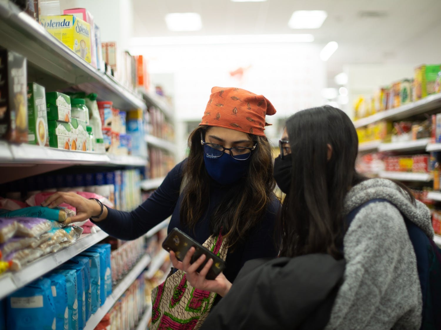 Juniors Pareen Bhagat (left) and Disha Dhamani (right) shop for food at the Target on Franklin Street on Friday, March 19, 2021.