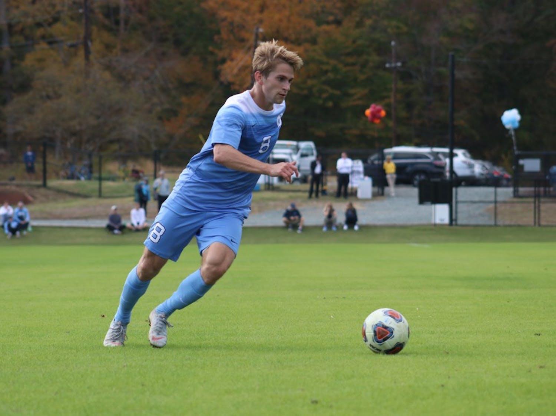 UNC midfielder Jack Skahan (8) drives the ball forward against Virginia Tech at Finley Fields on Nov. 4, 2018.