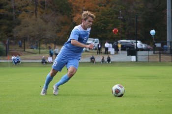 UNC midfielder Jack Skahan (8) drives the ball forward against Virginia Tech at Finley Fields on Nov. 4, 2018.
