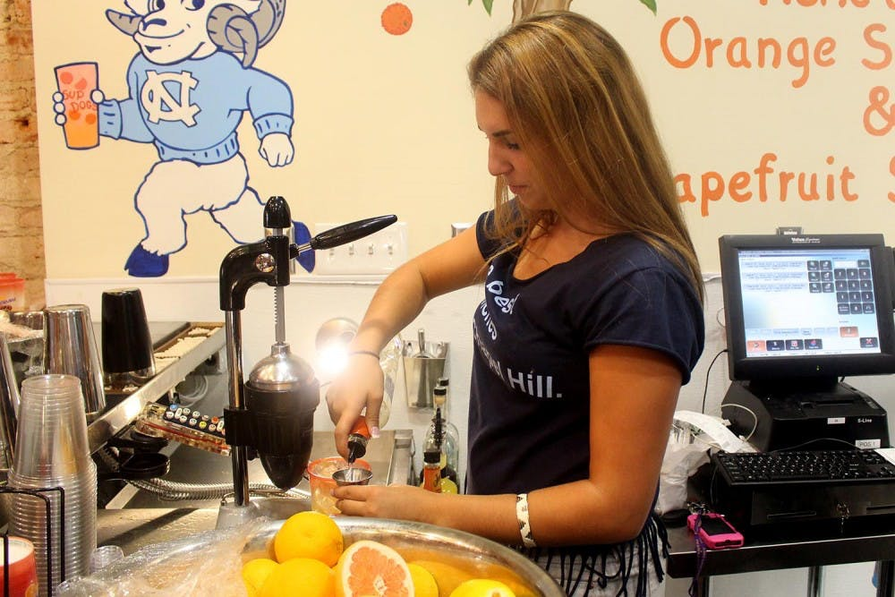 <p>Sup Dogs on Franklin Street opened Monday morning. Waitresses work on the signature orange crush behind a full bar inside the restaurant.</p>